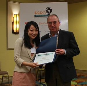Xue Doe accepts IPRRC Top Paper Award from Frank Ovaitt